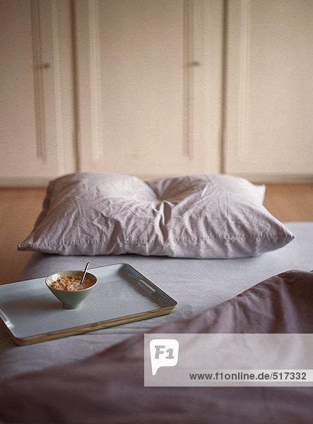 Frühstückstablett auf dem Bett sitzend