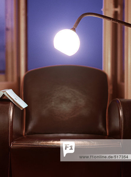 Light shining over chair with open book on arm