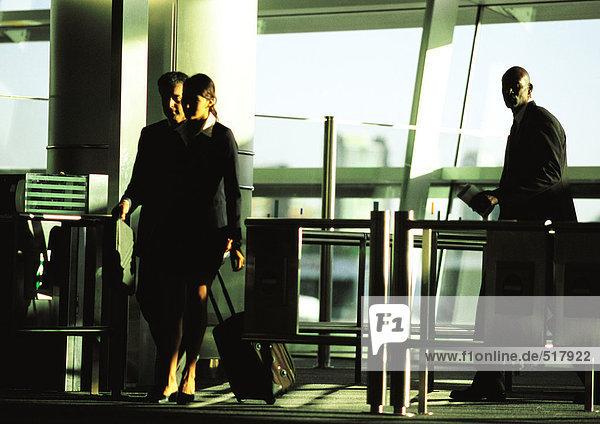 Geschäftsmann und Geschäftsfrau  die mit Koffern durch das Sicherheitstor gehen.