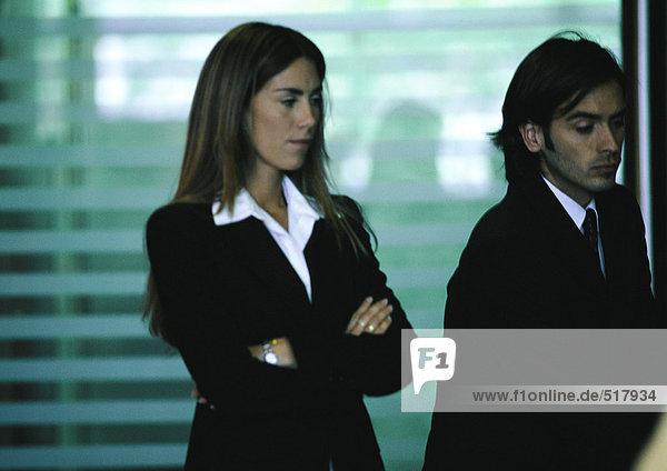 Geschäftsmann steht neben einer Geschäftsfrau mit verschränkten Armen.