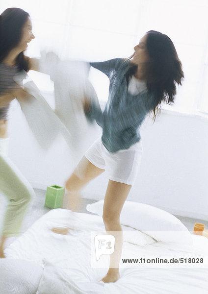 Zwei junge Frauen kämpfen mit Kissen,  verschwommene Bewegung