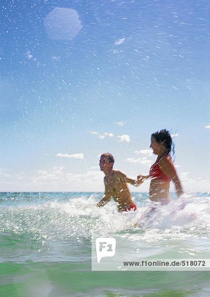 Couple splashing in sea