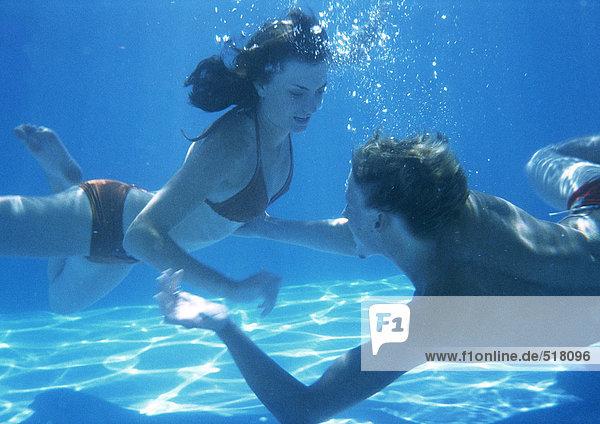 Mann und Frau schwimmen unter Wasser