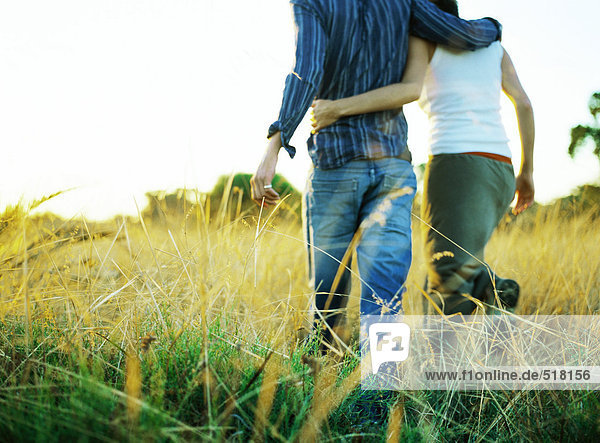 Paar geht durchs Feld  Rückansicht  tiefer Schnitt