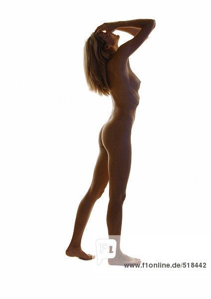 Nackte Frau stehend mit Kopf zurück und Händen auf dem Gesicht  volle Länge  Seitenansicht