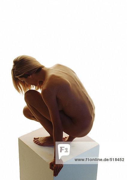 Nackte Frau mit geducktem Kopf auf Sockel  Seitenansicht