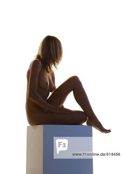 Nackte Frau sitzend mit Knie auf Sockel  Seitenansicht