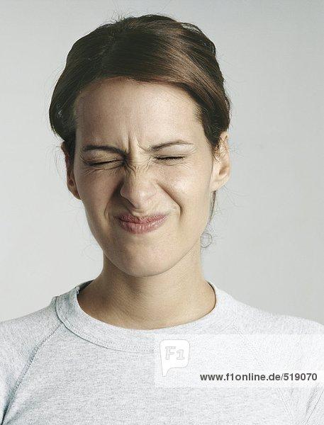 Junge Frau drückt die Augen zu  Nahaufnahme