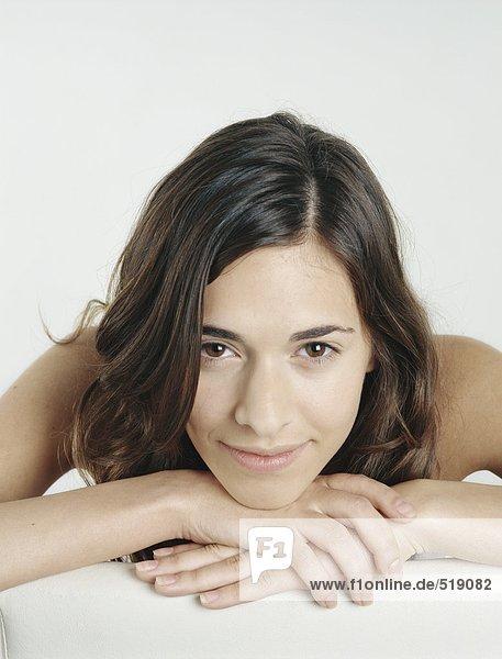 Frau mit nackten Schultern  die den Kopf auf umklammerten Händen ruht  lächelnd