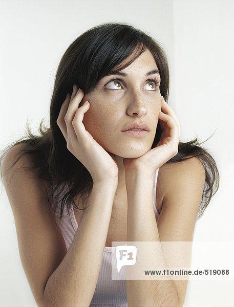 Frau schaut auf  hält das Gesicht zwischen den Händen.