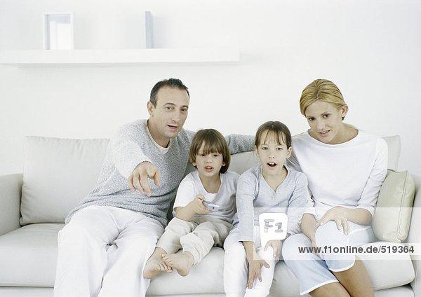 Eltern mit Tochter und Sohn auf dem Sofa sitzend  Vater geradeaus zeigend
