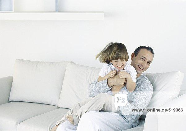 Vater hält Sohn auf Sofa