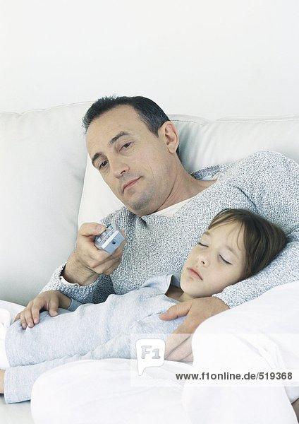 Mann auf der Couch sitzend  der auf die Fernbedienung zeigt und die schlafende Tochter auf dem Schoß hält.