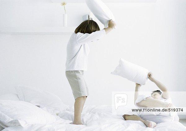 Jungen mit Kissenschlacht auf dem Bett