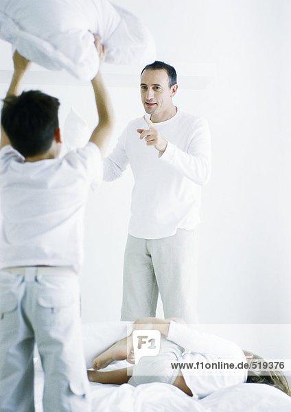 Junge auf dem Bett stehend  Kissen hochhaltend  Rückansicht  zweiter Junge auf dem Bett liegend  Mann auf den ersten Jungen zeigend