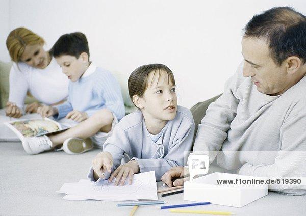 Mädchen und Vater auf dem Boden  Zeichnung  Mutter und Junge im Hintergrund lesen