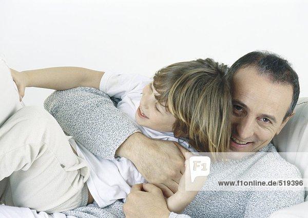 Vater hält den Sohn in den Armen und lacht.