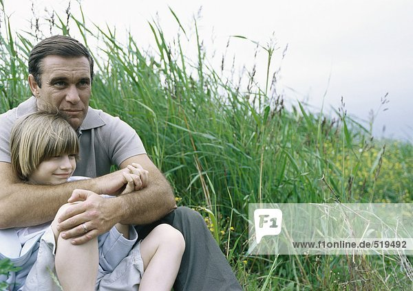 Man sitting on grass with arms around son