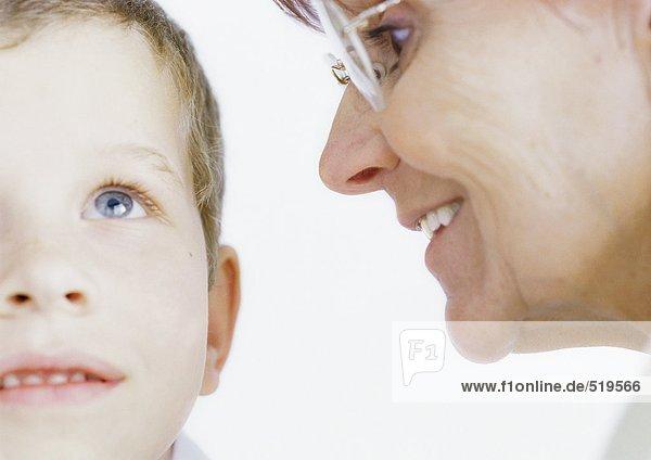 Großmutter flüstert dem Jungen ins Ohr.