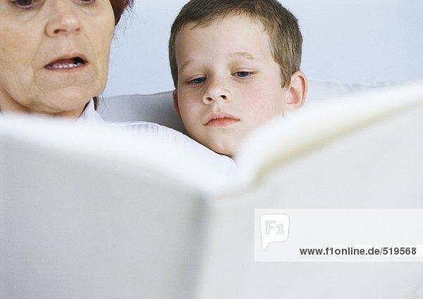 Großmutter liest Buch für Jungen
