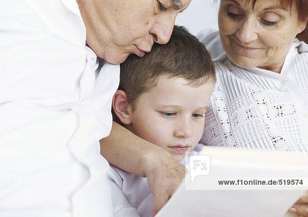 Großeltern beim Lesen mit Enkel