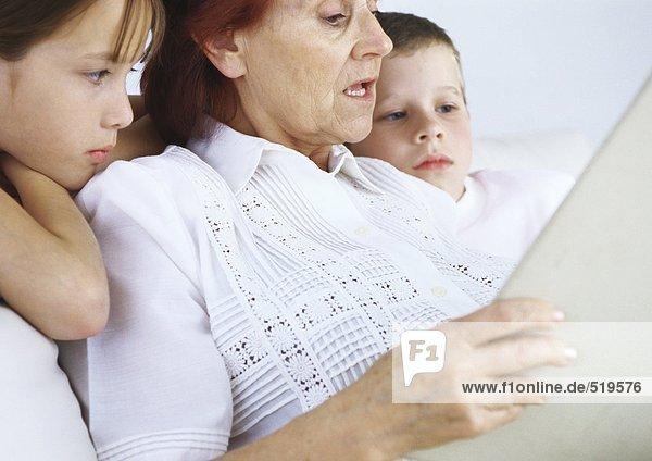 Großmutter liest Jungen und Mädchen vor.