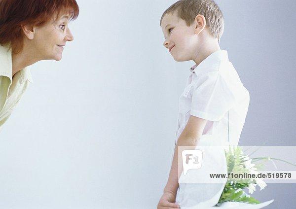 Junge überrascht Großmutter mit Blumenstrauß