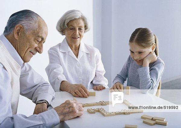 Großeltern und Mädchen am Tisch beim Domino spielen
