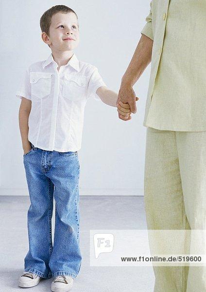 Junge hält die Hand des Mannes,  abgeschnitten