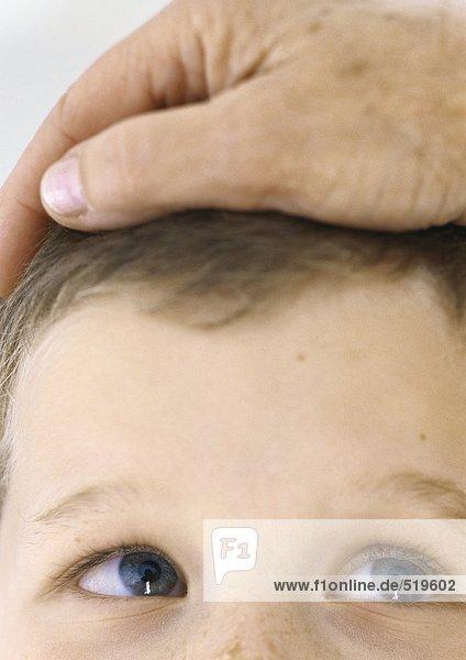 Erwachsenenhand auf Kinderkopf  Nahaufnahme