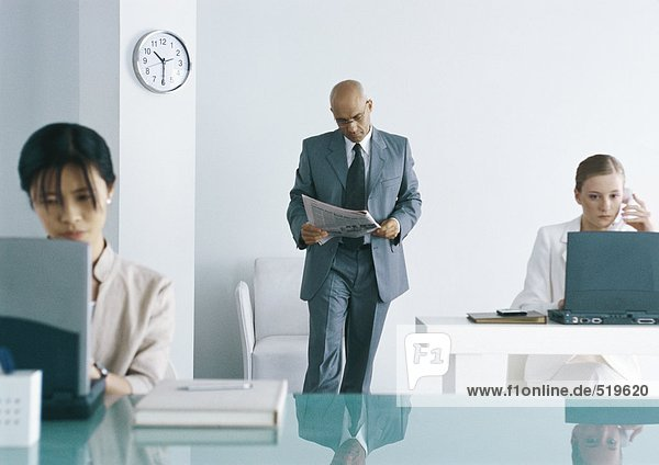 Männliche Führungskraft steht im Büro und liest Zeitung  weibliche Kollegen arbeiten am Laptop.