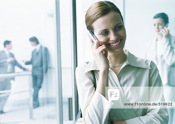 Businesswoman talking on cell phone in lobby  businesspeople in background