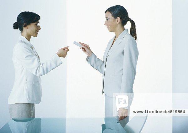 Frau überreicht zweite Frau Visitenkarte  Seitenansicht