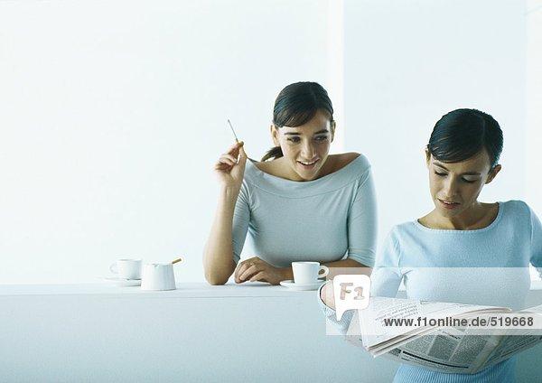 Zwei Frauen machen Kaffeepause  eine liest Zeitung  eine raucht.