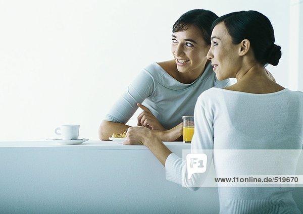 Zwei Frauen auf beiden Seiten der Bar beim Frühstück.