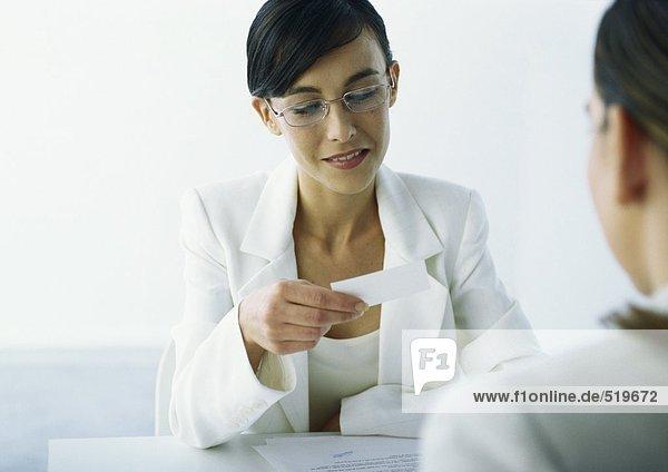 Frau schaut auf Visitenkarte  sitzt gegenüber der zweiten Frau