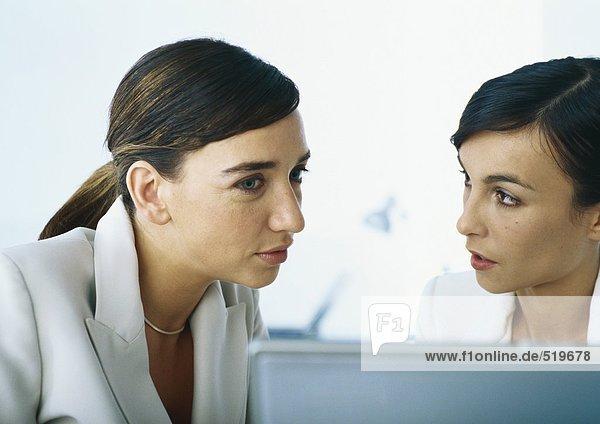 Zwei Geschäftsfrauen sprechen miteinander  Kopf und Schultern