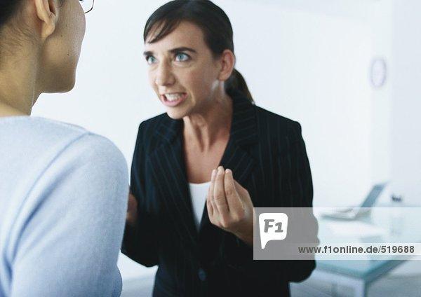 Geschäftsfrau spricht und gestikuliert wütend zur zweiten Frau