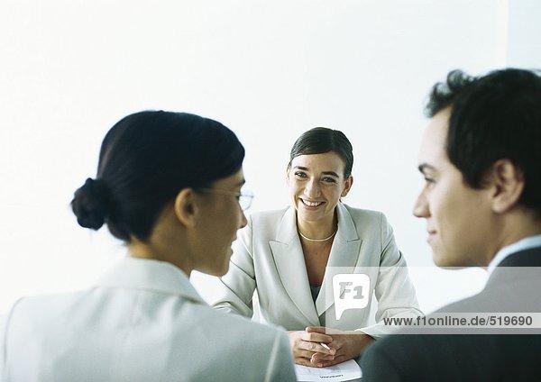 Mann und Frau lächeln sich an  sitzen sich gegenüber der lächelnden Geschäftsfrau.