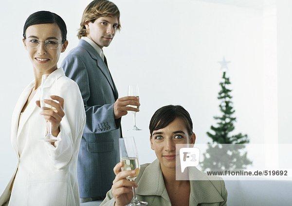 Geschäftsleute  die Champagnerflöten züchten  mit Weihnachtsbaum im Hintergrund