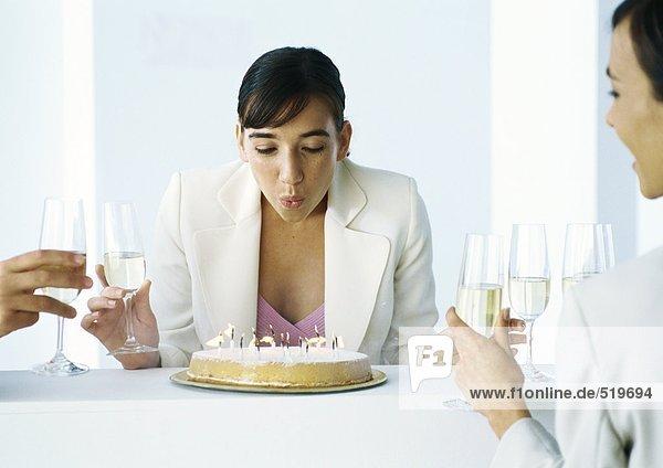 Frau bläst Kerzen auf Kuchen aus  sitzt mit anderen Leuten  hält Gläser Champagner.