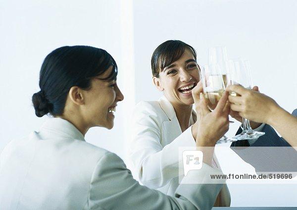 Geschäftsleute klirren und lächeln