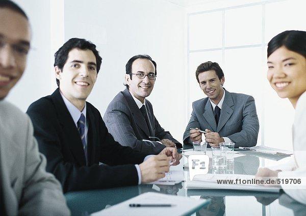 Geschäftsleute sitzen am Tisch und lächeln vor der Kamera.