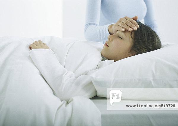 Mädchen liegt im Bett unter der Decke  die Hand der Frau auf der Stirn des Mädchens.