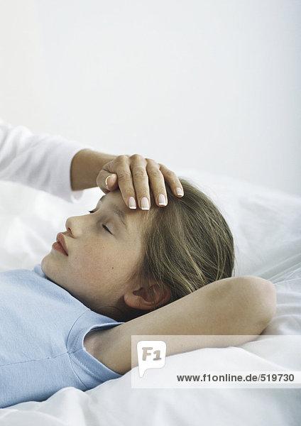Mädchen im Bett liegend mit Frauenhand auf der Stirn