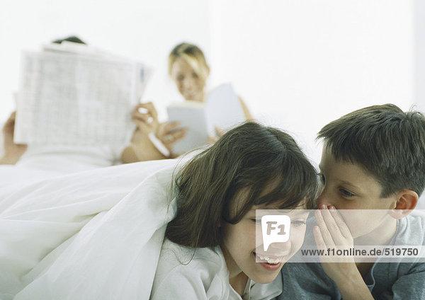Junge flüstert zu Mädchen  Eltern lesen im Hintergrund