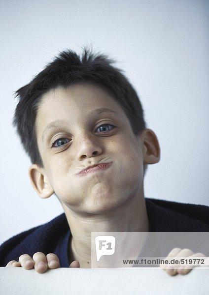 Junge bläst Wangen aus  Porträt