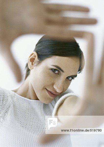 Frau rahmt mit den Händen  Porträt