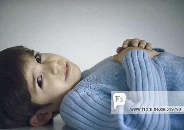 Junge liegend mit Händen auf der Brust