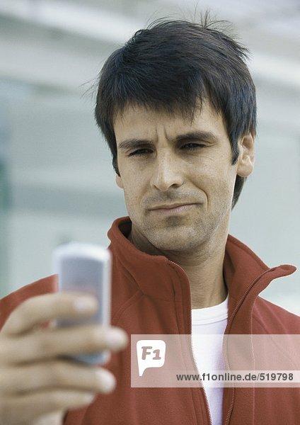 Mann schaut auf Handy